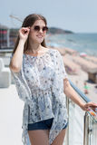 A beautiful young girl in summer clothes and in sun glasses on a luxury hotel background. The model woman in casual clothes. royalty free stock photography