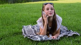 Beautiful young girl in summer dress lies on grass in park, using smartphone. stock video