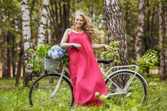 Beautiful young girl in a summer dress at sunset. Fashion photo in the forest. Model on a bicycle with flower bouquet, in a pink l stock image