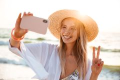 Beautiful young girl in summer hat and swimwear. Spending time at the beach, taking a selfie with outsretched hand Royalty Free Stock Photo