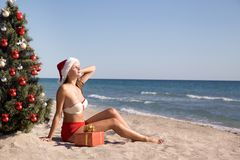 Beautiful young girl sunbathes on the beach at Christmas holidays. Beautiful young woman sunbathing on a tropical beach in the holidays with gifts under a Stock Photo