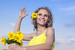 Beautiful young girl with sunflowers. On a background clouds Royalty Free Stock Photos