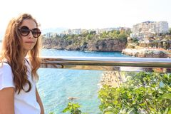Beautiful young girl in sunglasses on the balcony overlooking the Mediterranean port with yachts in Antalya stock image