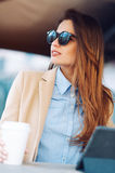 Beautiful and young girl in sunglasses drinking coffee in the street and reading the news in a tablet Stock Image