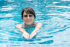 Beautiful young girl in sunglasses floating in the pool Stock Photo