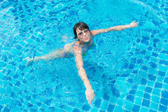 Beautiful young girl in sunglasses floating in the pool Stock Photography