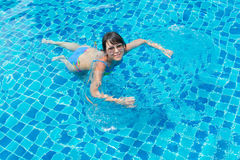 Beautiful young girl in sunglasses floating in the pool Royalty Free Stock Photography
