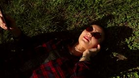 Beautiful young girl in sunglasses lying on grass and listening to music on her phone. stock footage
