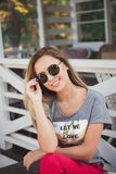Beautiful young girl in sunglasses. She`s smiling. Grey t-shirt. The girl has blonde long hair royalty free stock photography