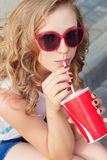 Beautiful young girl in sunglasses sitting on the street and drink a coke with a paper Cup from the tube Stock Images