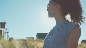 Beautiful young girl in sunglasses talking on the field. sunlight glare and dynamic shooting stock video footage