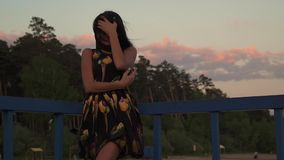 Beautiful young girl at sunset posing at the camera and smiling. Silhouette of a beautiful girl in a light dress at. Silhouette of a beautiful girl in a light stock video