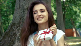 Beautiful young girl surprise catches gift sitting on the grass in the Park. In the summer stock video footage