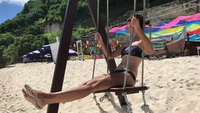 Beautiful young girl swing at the beach on a tropical island of Bali, Indnonesia. Ocean, sky, 4K, smooth motion. Asia. Beautiful young girl swing at the beach stock video