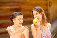 Beautiful young girl taking a bite of an apple. Other girl wishes to eat apple too Stock Image