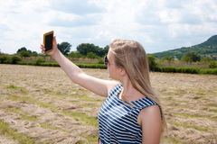 Beautiful young girl taking a selfie in the countryside Royalty Free Stock Photos
