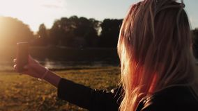 Beautiful young girl taking selfie at sunset. HD stock footage