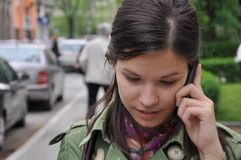 Beautiful young girl talking on mobile phone. In the city area Royalty Free Stock Photo