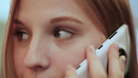 Beautiful young girl talking on mobile phone. Face close-up. stock video