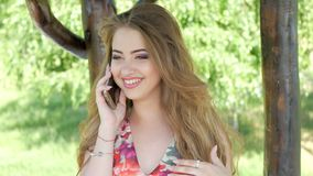 Beautiful young girl talking on mobile phone stock footage
