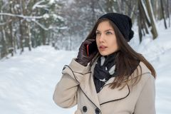 Beautiful young girl talking on the phone outside in a snowy for stock image