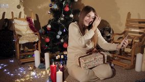 Beautiful young girl talking in skype unpacking a new year gift stock video