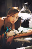 Beautiful young girl tattoo artist portrait during creation tattoo on a man`s hand. Royalty Free Stock Photo