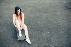 Skateboarder girl smiling. Hipster girl sitting on skateboard. Beautiful young girl with tattoos sits on longboard in sunny weather Royalty Free Stock Photo