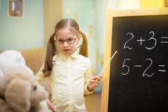 Beautiful young girl is teaching toys at home on blackboard. Preschool home education. Little teacher in glasses. Beautiful young girl is teaching toys at home stock photos
