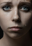 Beautiful young girl with tears in her eyes. Violence and abuse of girls theme: portrait of a beautiful young girl with tears in her eyes, a beautiful sad girl Stock Photos
