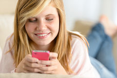 Beautiful young girl texting on her cellphone Royalty Free Stock Photo