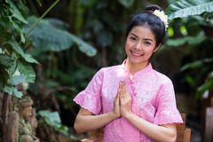 Beautiful young girl in thai traditional dress welcome smile royalty free stock images