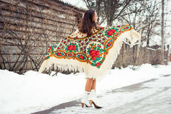 Beautiful young girl with traditional Russian or Ukrainian scarf in winter dances and celebrates. Stock Photo