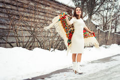 Beautiful young girl with traditional Russian or Ukrainian scarf in winter dances and celebrates. Royalty Free Stock Images