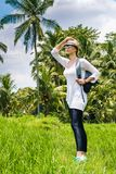 Beautiful young girl traveler in hat, glasses, with backpack walks along a rice field with green grass, palms, sky Bali Indonesia