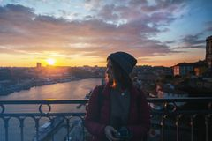 Beautiful young girl traveler standing at sunset overlooking the royalty free stock photo