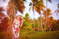 Beautiful young girl in tropical palm grove, summer breeze Stock Image