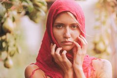 Beautiful young girl trying on a red scarf. Autumn time for harvest. Orchard. The concept of harvesting.  Stock Images