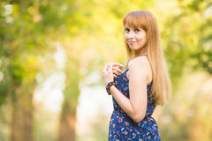 Beautiful young girl turned and looked up with a smile in the frame on the background of the sunny blurred greenery Royalty Free Stock Photo