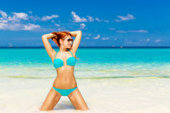 Beautiful young girl in turquoise bikini on a tropical beach. Bl Royalty Free Stock Image