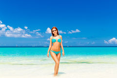 Beautiful young girl in turquoise bikini on a tropical beach. Bl Stock Images