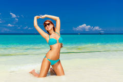 Beautiful young girl in turquoise bikini on a tropical beach. Bl. Ue sea in the background. Summer vacation concept Royalty Free Stock Images