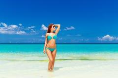 Beautiful young girl in turquoise bikini on a tropical beach. Bl Stock Photography