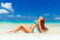 Beautiful young girl in turquoise bikini on a tropical beach. Bl Royalty Free Stock Photography