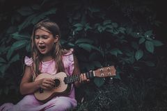 Beautiful young girl with ukulele. Beautiful young girl with blond hair wearing pink dress playing ukulele and singing song on dark nature background. Grape stock images