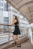 Beautiful young girl using headphones listening to music and looking something. In the city stock photography