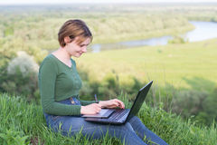 Beautiful young girl using her graphic tablet sitting in the grass near river stock image