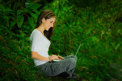 Beautiful young girl using laptop outdoors in the Royalty Free Stock Images