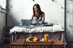 Girl in bed. Beautiful young girl is using a laptop and smiling while sitting in bed at home Royalty Free Stock Photo