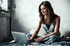 Girl in bed. Beautiful young girl is using a laptop and smiling while sitting in bed at home Royalty Free Stock Photography